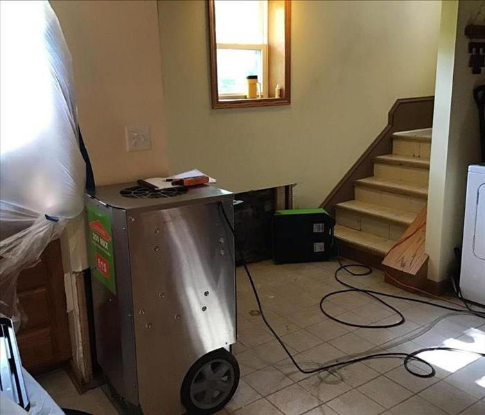 Silver and green dehumidifier on a tile floor with a stairway and a green air mover on the floor.