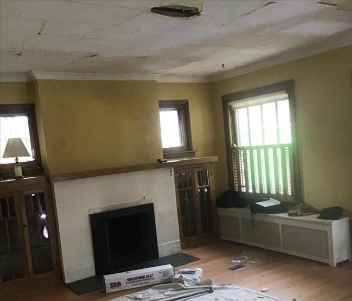 Dining room with a fireplace, yellow walls and a hole in the ceiling with debris on a tarp on the floor.
