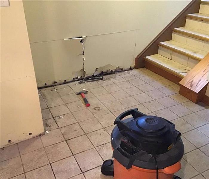 Dirty tile floor with white drywall with holes at he bottom with a stairway and an orange shop vac on the floor.