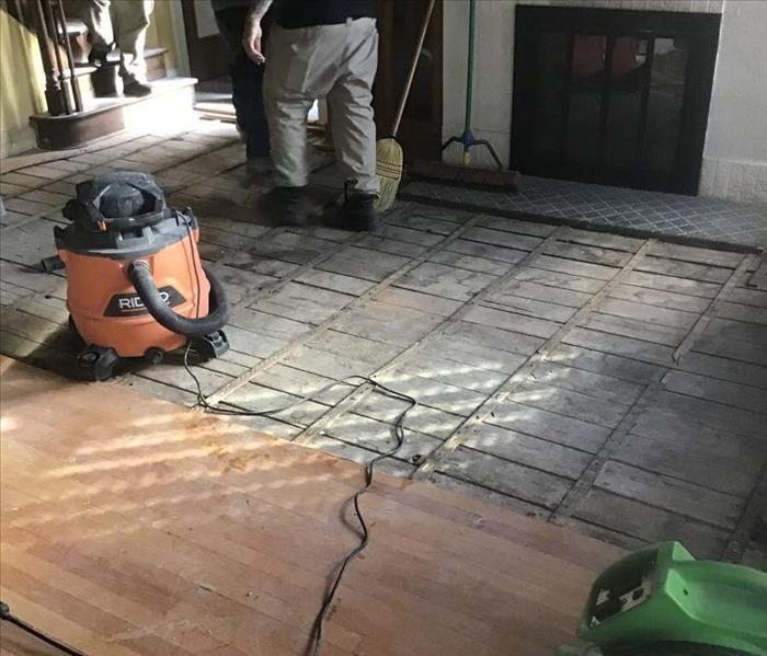 Hardwood floor partially removed in front of a fireplace, with a green air mover and a orange shop vacuum.