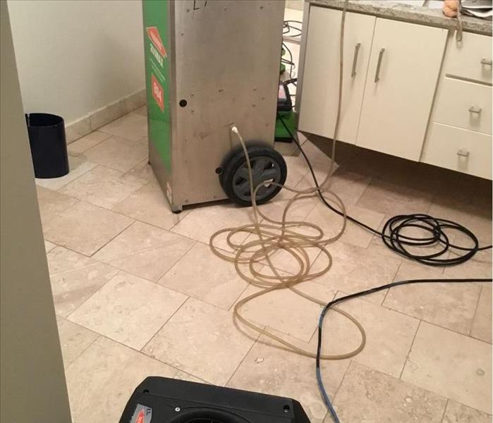 Clean light tan tile with a SERVPRO dehumidifier and a black air mover in a bathroom with white cabinets.