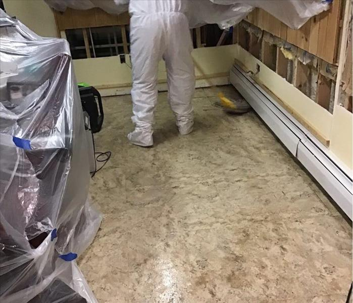 Dirty tile floor with a yellow bucket and a worker in a white protective suit mopping the floor.