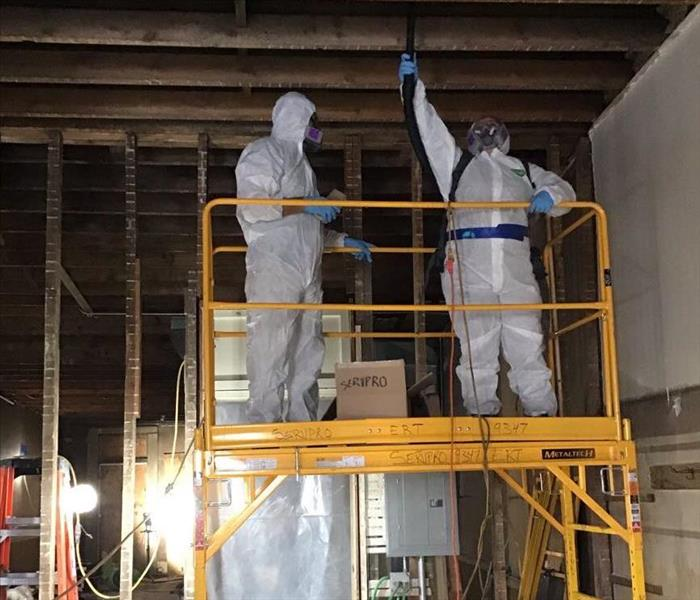 Yellow industrial ladder with 2 workers wearing protective suits cleaning the ceiling.