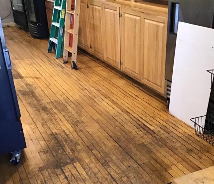 Soot covering a hardwood floor with light brown cabinets and 2 ladders in the background.