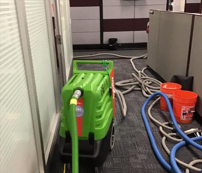 Big green water extractor in a hallway of an office with wet grey carpet and white walls with orange buckets and hoses.