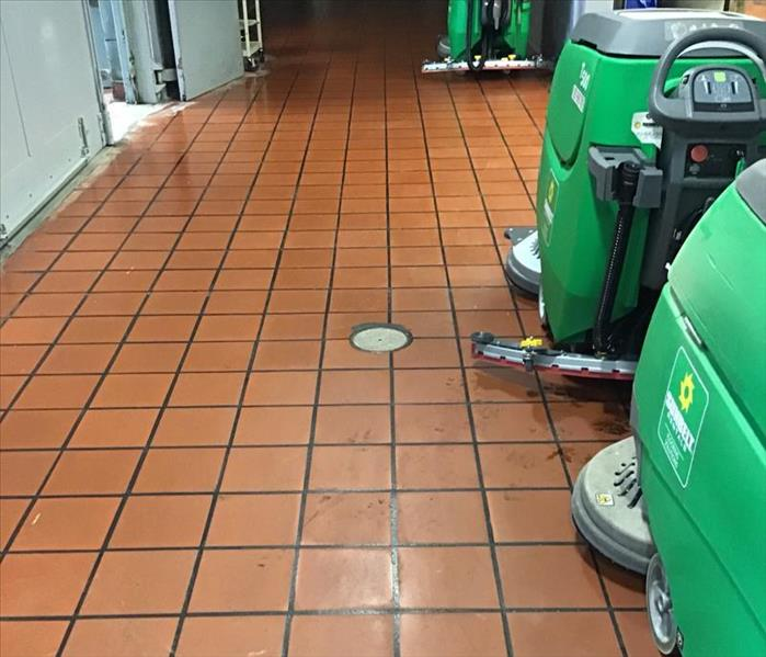 Brown tile floor of a warehouse with green cleaning machines cleaning the floor.