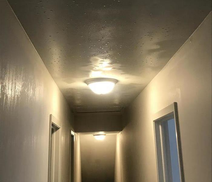 Soaking wet ceiling of a hallway with two light fixtures with white walls.