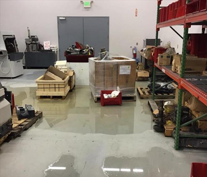 Water on the floor of a warehouse with orange shelves and boxes and wood pallets on the floor.