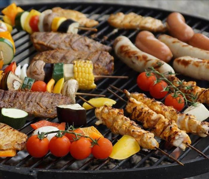 Meat and vegetables on a black round grill.