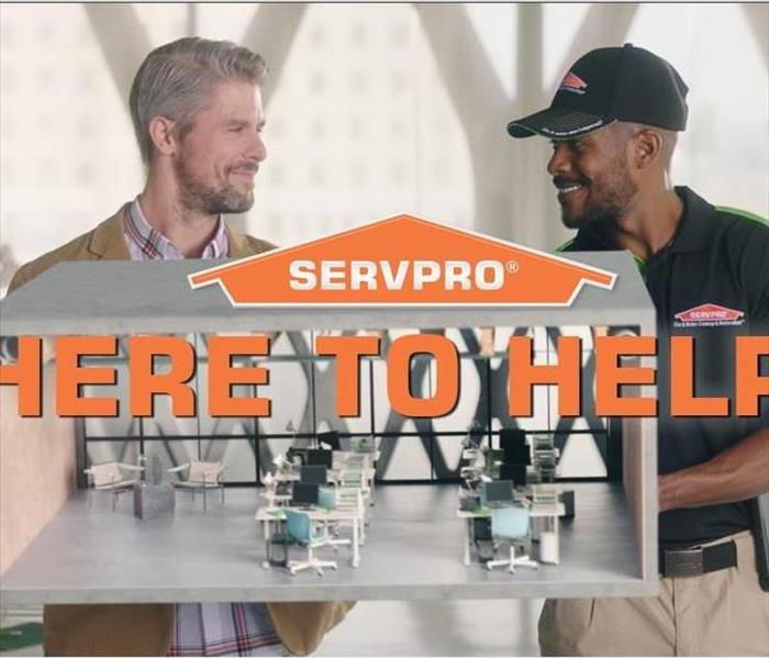 SERVPRO orange house logo with here to help with a SERVPRO employee and a customer in the background.