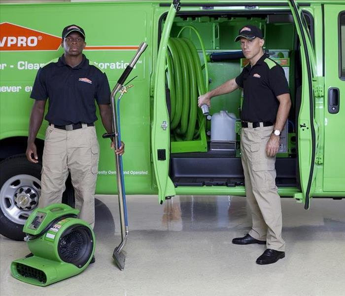 Two SERVPRO employees standing outside a van with an air mover on the ground.