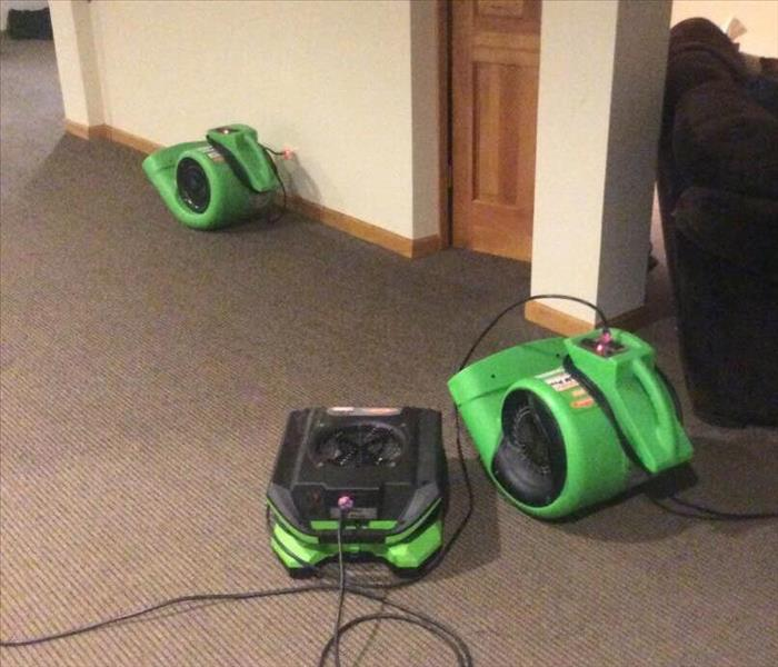 Three green air movers on wet grey carpet with white walls and a wood door.